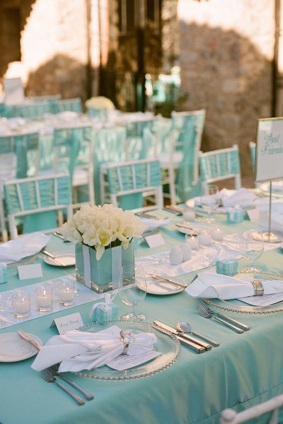 a tiffany blue and white table setting with white tulips in the box, signs, candles and white napkins