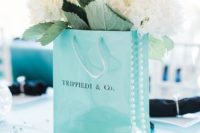 a tiffany blue paper bag centerpiece with white hydrangeas and greenery, pearls and sunglasses