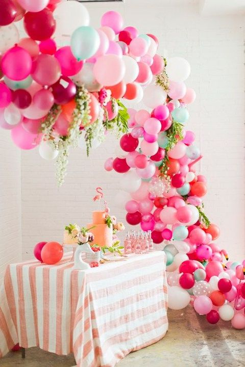 a tropical bridal shower dessert table accented with a super colorful balloon garland over it