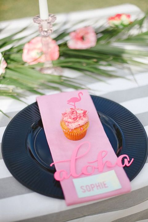 a tropical bridal shower place setting with a black charger, a pink napkin and cupcake with a flamingo topper
