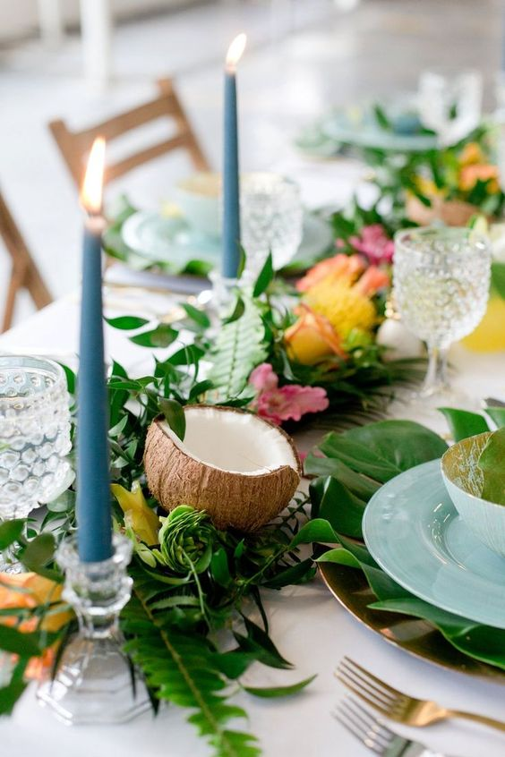 a tropical bridal shower table setting with greenery, coconuts, blooms and blue candles and porcelain