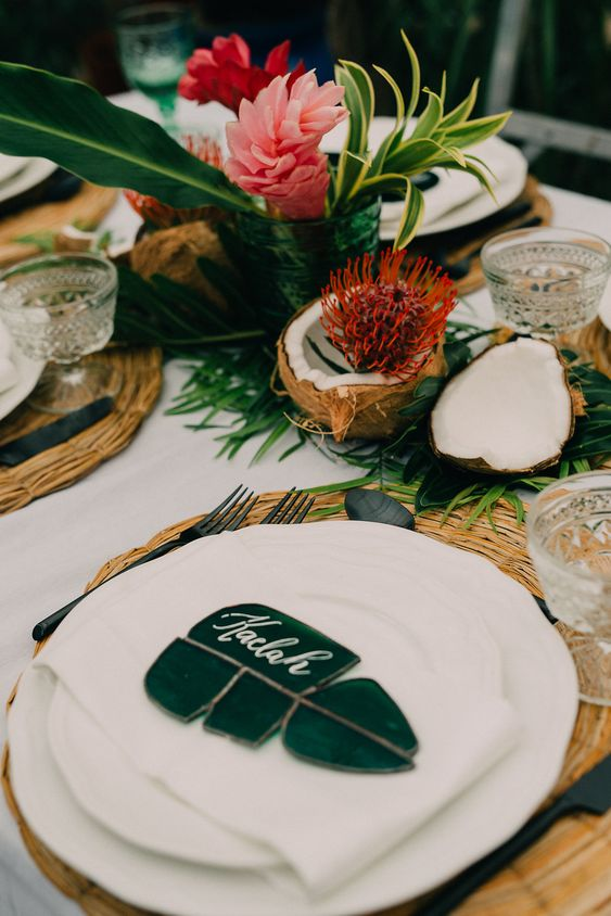 a tropical bridal shower tablescape with greenery, tropical blooms, coconuts, proteas, tropical leaves and wicker chargers