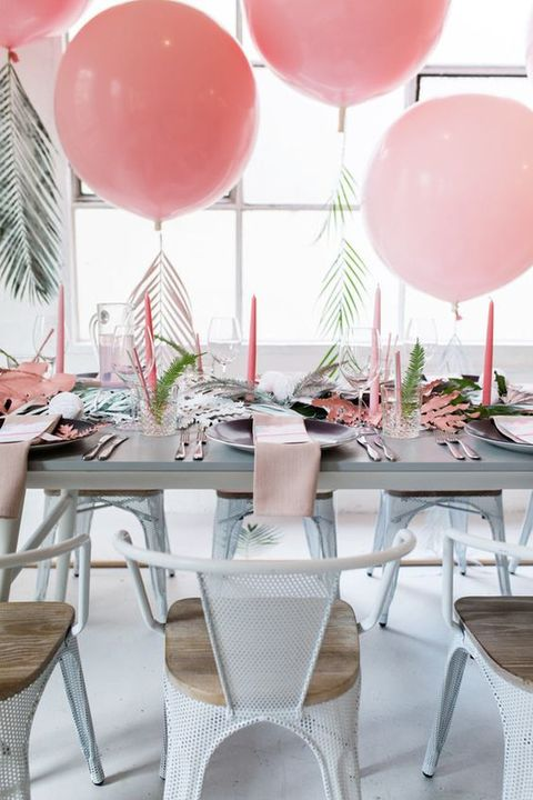 a tropical bridal shower tablescape with pink candles, napkins, balloons with tropical leaves and some greenery