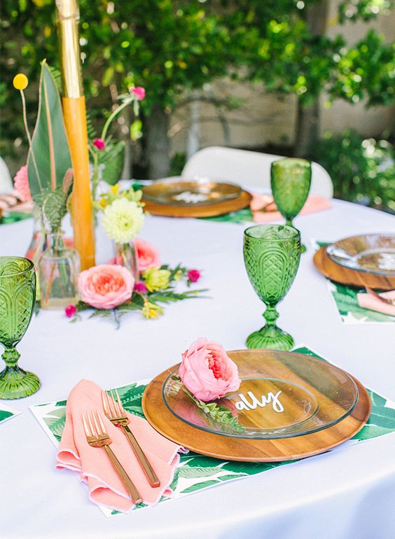 a tropical bridal shower tablescape with wooden chargers, glass plates, greneery and bright blooms and pink napkins