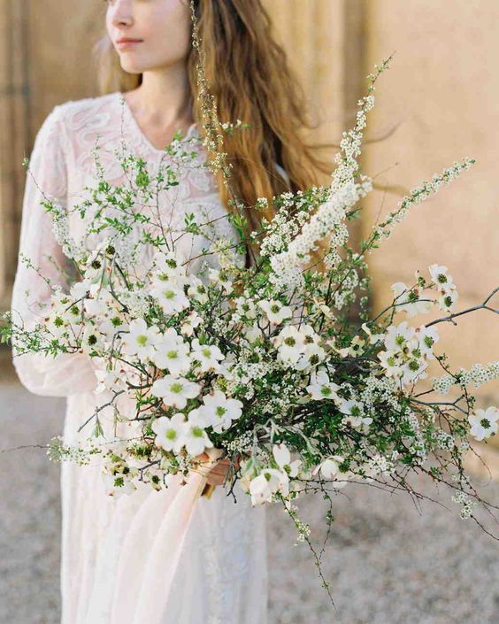 a unique spring-like wedding bouquet of various kinds of blooms and greenery looks wild
