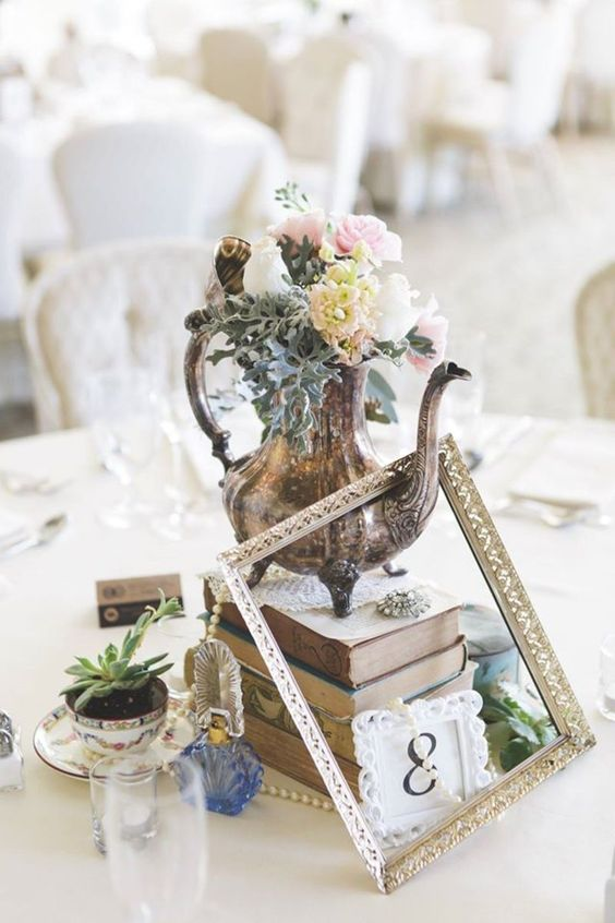 a unique wedding centerpiece of a stack of books, a frame, a silver teapot with blush blooms, succulents and a table number