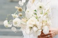a unique white wedding bouquet of lunarias, white blooms and various dried herbs for an airy look