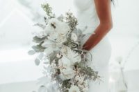 a uniquely shaped white wedding bouquet of roses, peonies and other blooms plus pale cascading greenery