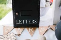 a vintage metal mailbox with white letters, a bunting, some cards and colorful posies