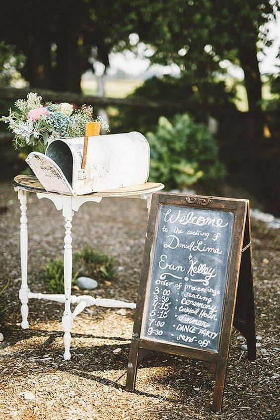 a vintage whitewashed mailbox placed on a side table, pastel blooms next to it and a chalkboard sign