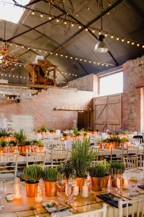 a wedding centerpiece made of potted greenery in copper pots and candles in jars is a cool idea