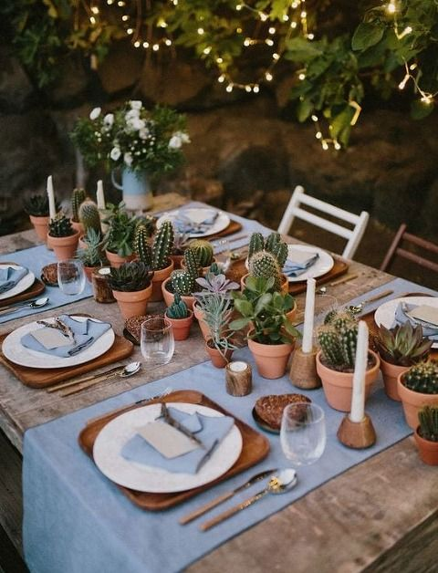 a wedding table runner made of potted cacti and succulents plus white candles is ideal for a desert wedding