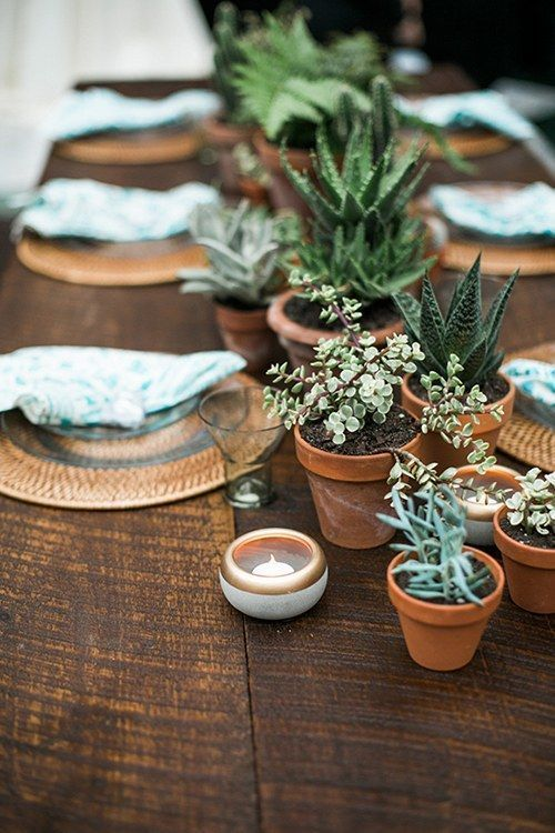 a wedding table runner of potted greenery and succulents plus candles is a cool idea for a modern wedding