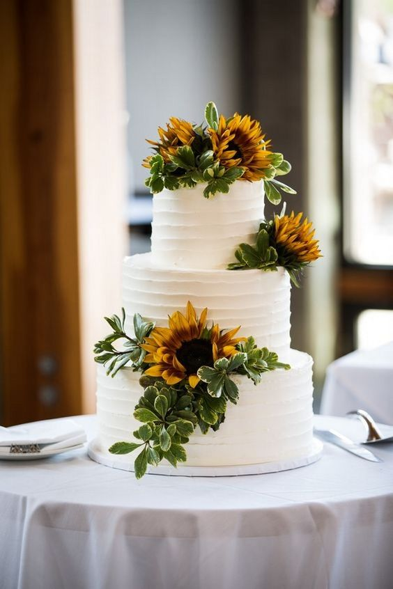 a white textural wedding cake decorated with greenery and sunflowers for a bold and cool look