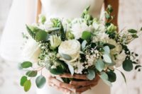 a white wedding bouquet with peonies and roses, greenery and much texture and with a white lace wrap