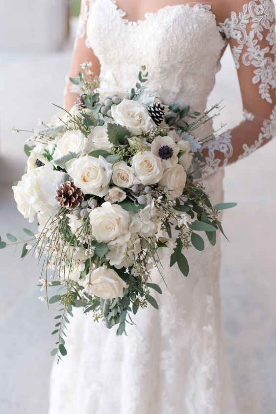 a white winter wedding bouquet with roses, hydrangeas, berries, pinecones and pale greenery
