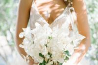 an airy lunaria and berries wedding bouquet with a sheer white ribbon is a beautiful and breezy idea