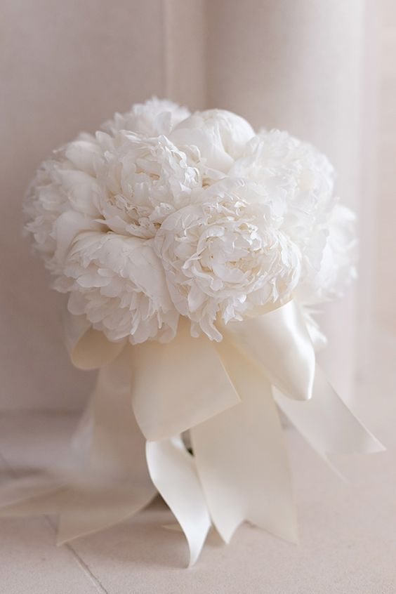 an airy white wedding bouquet of peonies and white silk ribbons is a heavenly beautiful idea