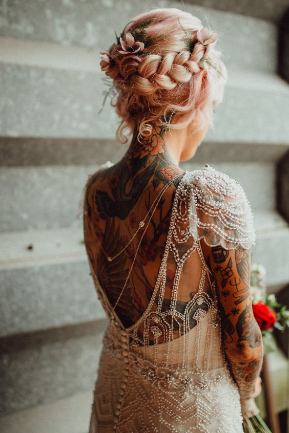 an art deco wedding dress with back necklaces and tattoos and pastel pink bridal hair – an updo with a braided halo and some blooms