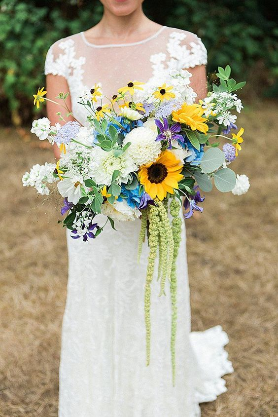 an elegant and colorful wedding bouquet of white and purple blooms, sunflowers, various kinds of greenery