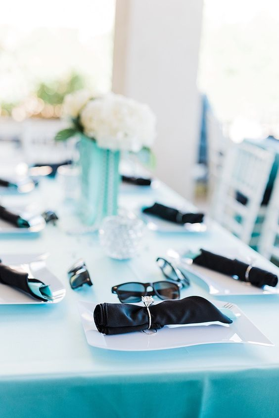 an elegant bridal shower tablescape with a tiffany blue tablecloth, black napkins with rings, white blooms and sunglasses