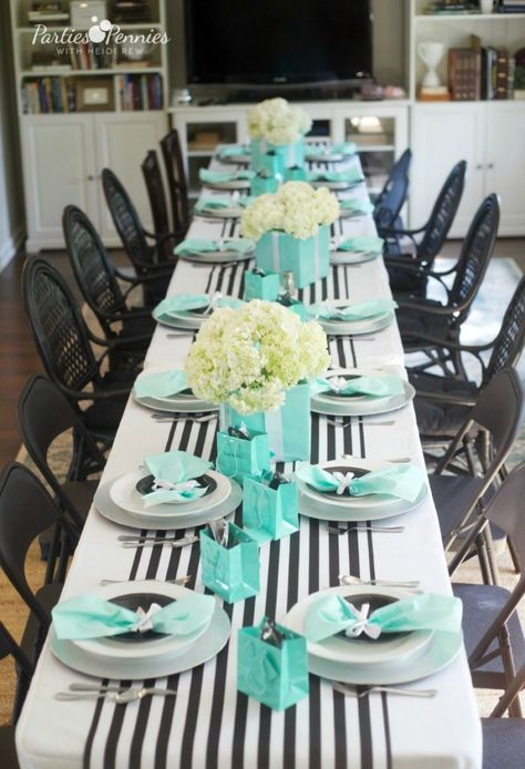 an elegant table setting with a striped black and white table runner, white and black plates, tiffany blue napkins and paper bags plus white bloom centerpieces