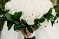 an elegant white rose wedding bouquet with greenery and a white ribbon wrap is a timeless idea