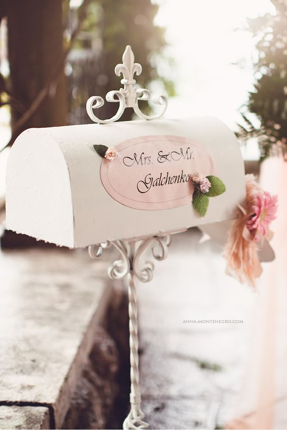 an elegant white vintage mailbox with a pink sticker with the couple's names and some pink blooms and greenery