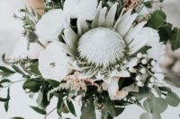 an oversized wedding bouquet of a king protea, white peonies, berries, thistles and greenery for a bold statement