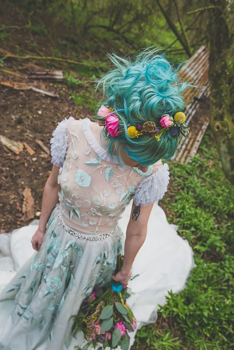 blue hair in a whimsical twisted and wavy updo with a colorful floral crown matching a blue floral applique wedding dress