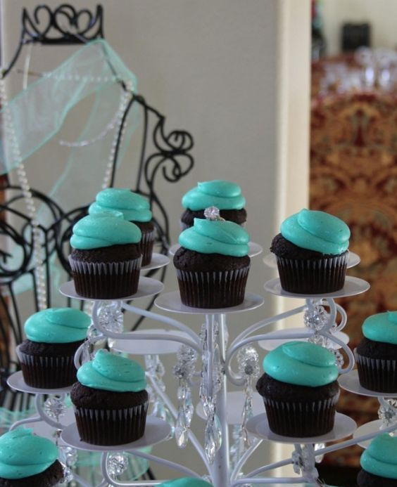 chocolate cupcakes with tiffany blue icing and diamond rings as toppers
