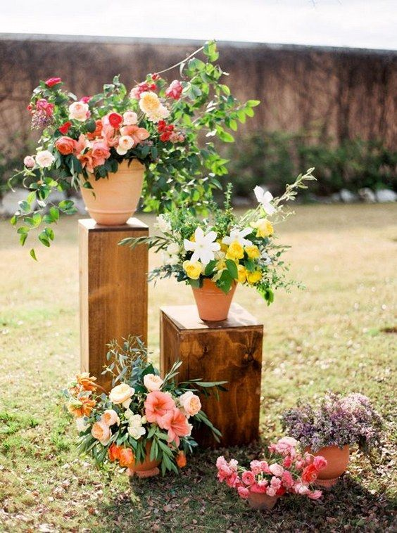 colorful blooms in pots on stands are nice for decorating a space, whether it's a reception or a ceremony space