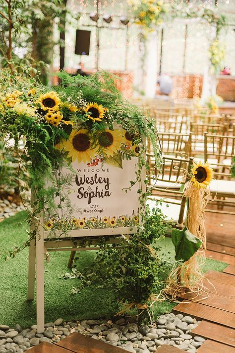 cool rustic wedding decor of greenery and sunflowers put on a wedding sign with painted sunflowers
