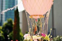 a dreamy hot air balloon wedding centerpiece with fresh flowers and greenery for a modern wedding