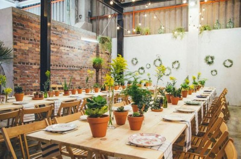 potted flowers and greenery lining up the wedding reception tables and greenery wreaths that refresh the space