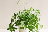 potted greenery with a wire table number is a cool wedding decoration or centerpiece