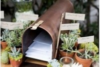 a box with wedding cards and potted greenery and succulents for decorating