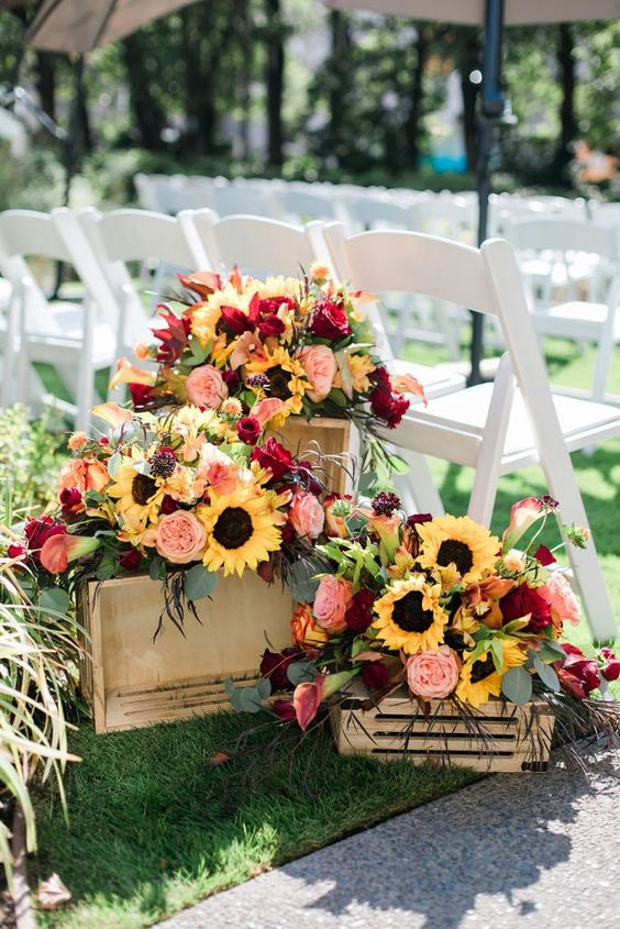 lush and bright wedding decor of sunflowers, blush and burgundy blooms, greenery and dark herbs