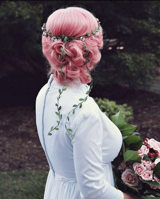 pink hair in a wavy and curly low updo plus a greenery ribbon for a modern boho bridal look