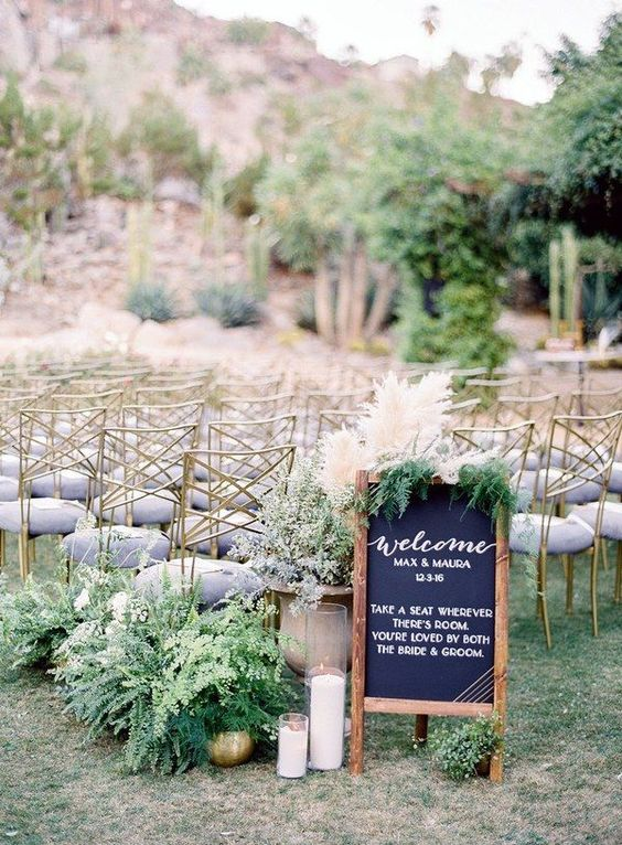 potted greenery and candles decorate the wedding ceremony space and a chalkboard sign adds to it
