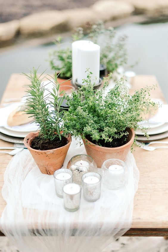 potted greenery and lots of candles plus an airy table runner make the little table alive and very fresh