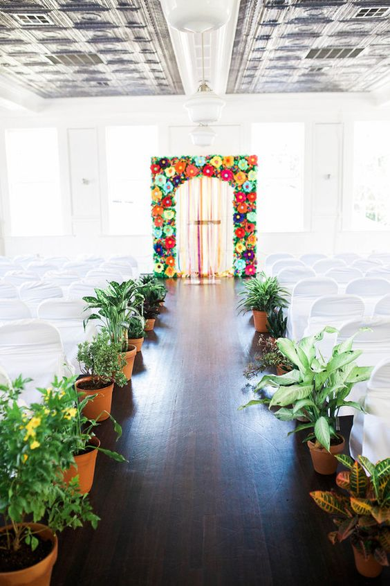 potted plants and flowers line up the aisle and make it bold and outdoorsy, though it's indoors