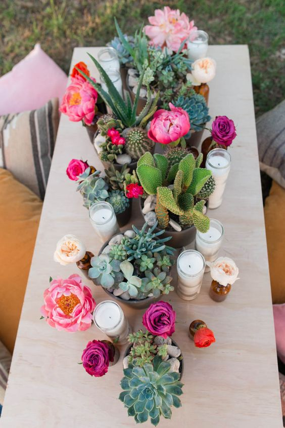 potted succulents and cacti plus blooms and candles make the table super bold, bright and cheerful