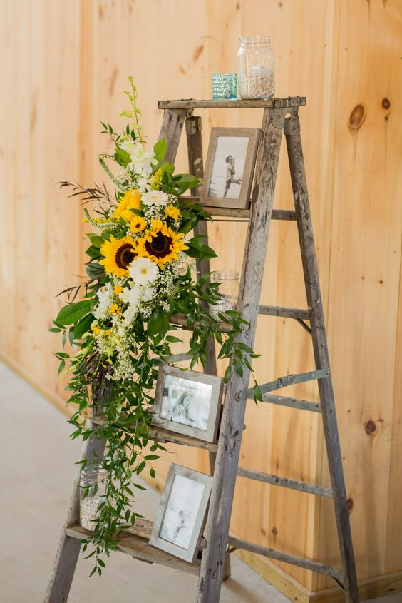 rustic wedding decor of a ladder, greenery, photos and sunflowers and white blooms