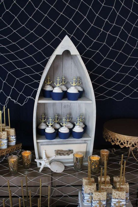 serve your cool cupcakes with anchor toppers in a cool boat and style your dessert table with net, candles and starfish