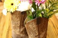 cowgirl boots with brigth blooms and greenery can be nice decorations or centerpieces for a themed shower