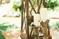 candles in wooden candleholders and a large candle lantern with greenery for styling the table