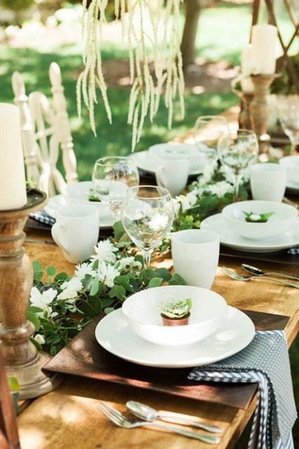 a cozy rustic setting with a greenery and white bloom runner, candles in wooden candleholders, printed napkins