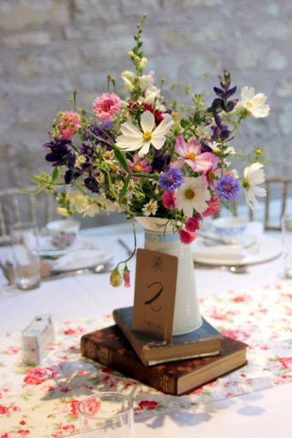 Table numbers with white jug and bright flowers