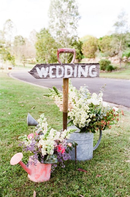 wedding sign with flowers in water cans